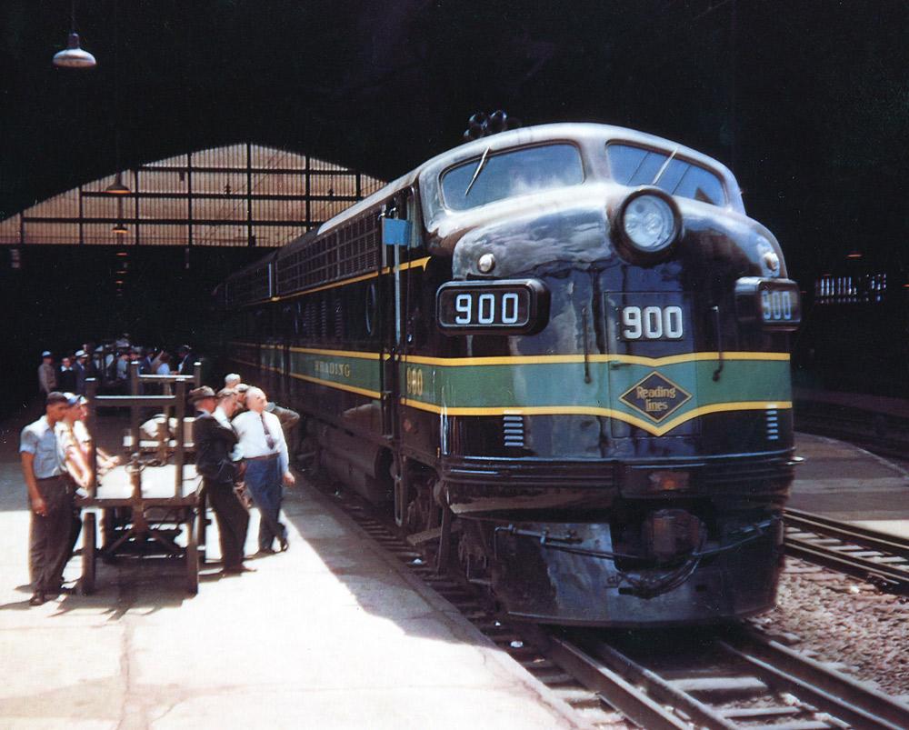Color photo of streamlined diesel locomotive under arched trainshed