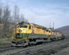 Color photo of three road-switcher diesel locomotives with Reading Company freight train