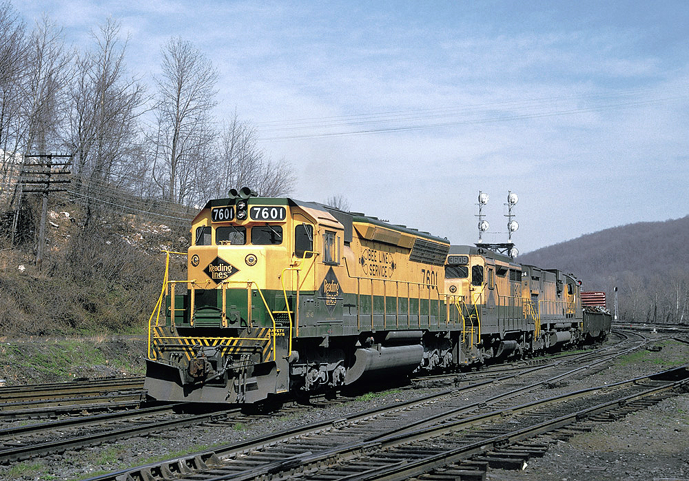 Color photo of three road-switcher diesel locomotives with Reading Companyfreight train
