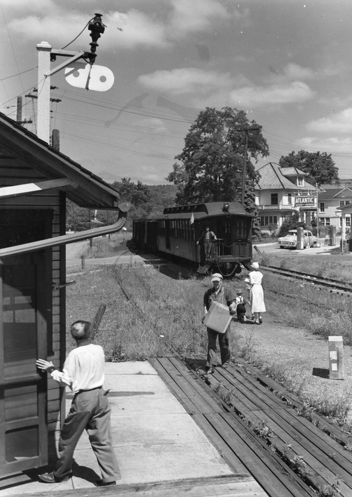 Man at station with train stopped yards away.