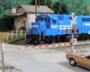 A bright blue Conrail diesel crosses a road in front of an old-fashioned white clapboard Post Office