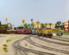 A modern yellow-and-gray diesel pulls a manifest freight past a busy highway lined with businesses