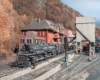 A steam locomotive pulls a string of flatcars loaded with military vehicles through an Appalachian town in autumn