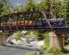 A steam locomotive pulls a string of loaded log cars over a steel trestle above a creek in a forest