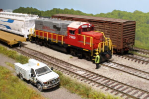 Model locomotive with model person next to it on a layout