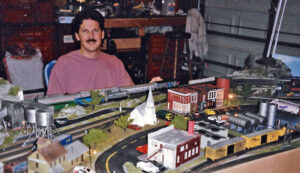 Man sitting next to an HO scale layout in a garage