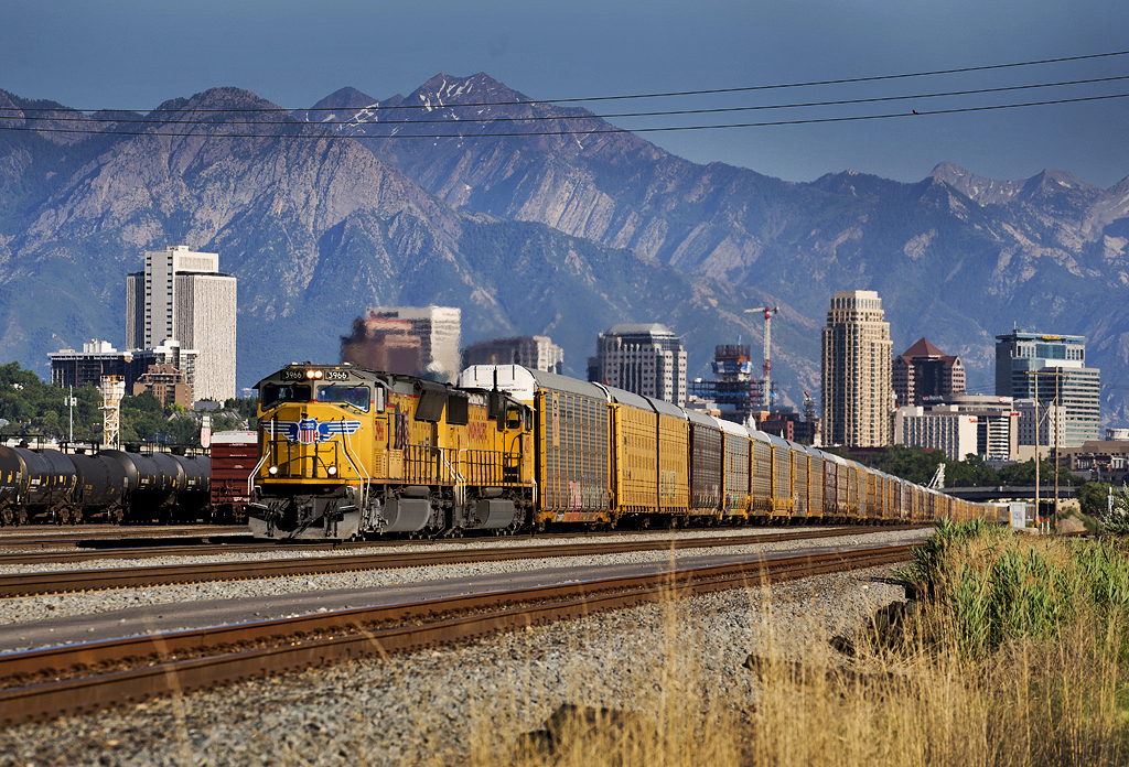 Train with yellow diesels against skyline and mountains