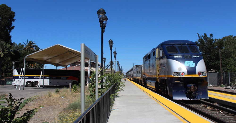 Passenger train stopped at station with bus waiting across platform