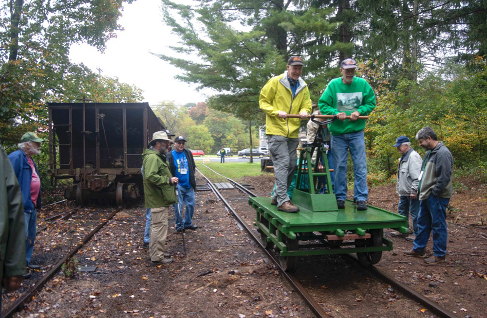 Men ride handcar as others look on