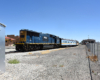 Blue and yellow locomotive shoves passenger cars on a rail siding.
