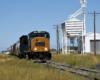 A locomotive hauls a freight train in a flat landscape.