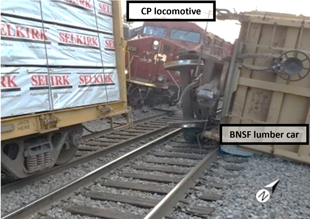 Derailed locomotive and freight car on adjacent tracks