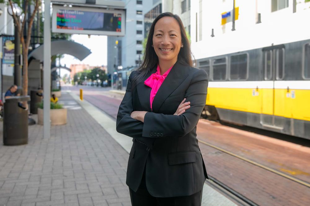 Woman standing next to light rail line