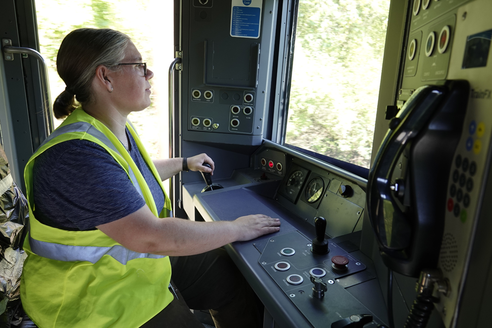 Woman in high-visibility vest at controls of railcar