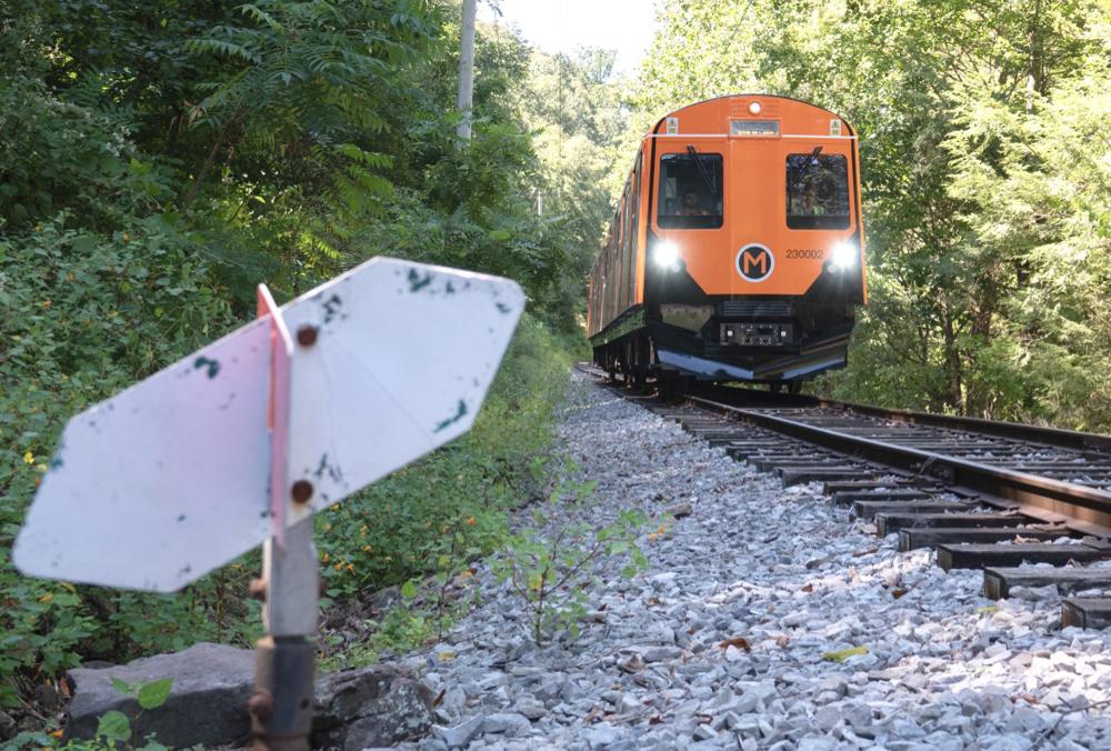 Orange railcar approaches switch on rail line surrounded by trees