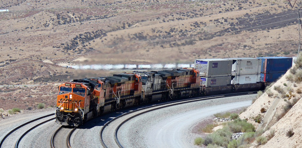 Intermodal train with four locomotives rounds curve