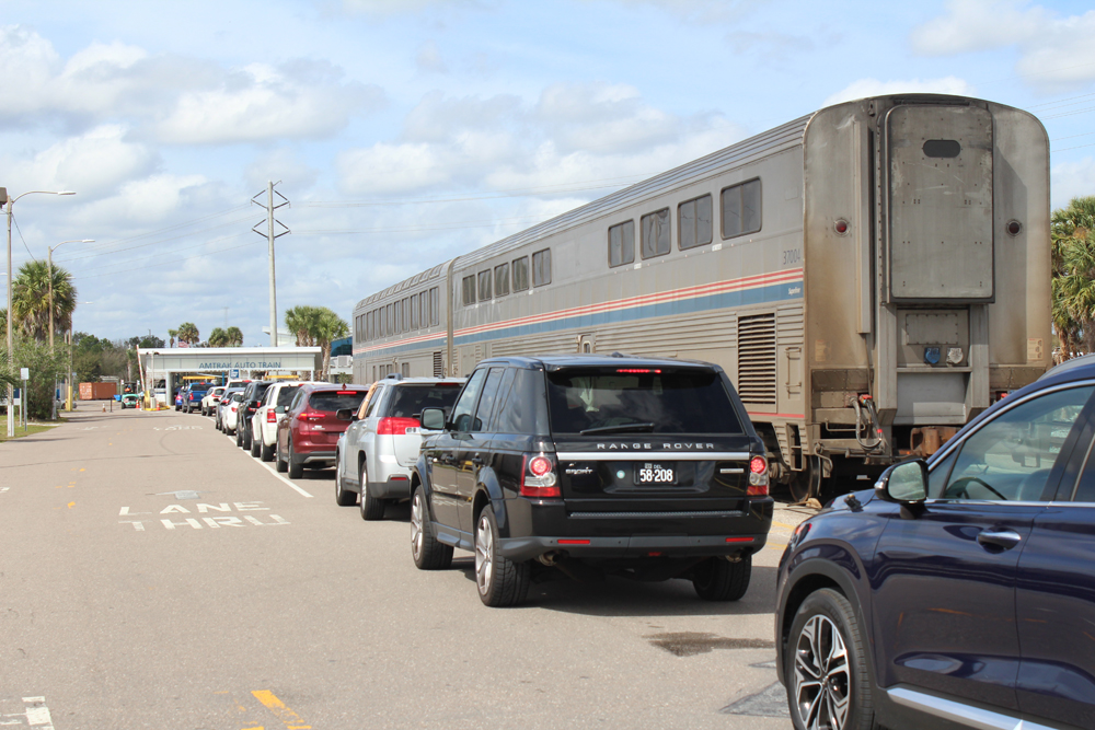 Cars lined up on road next to passenger train