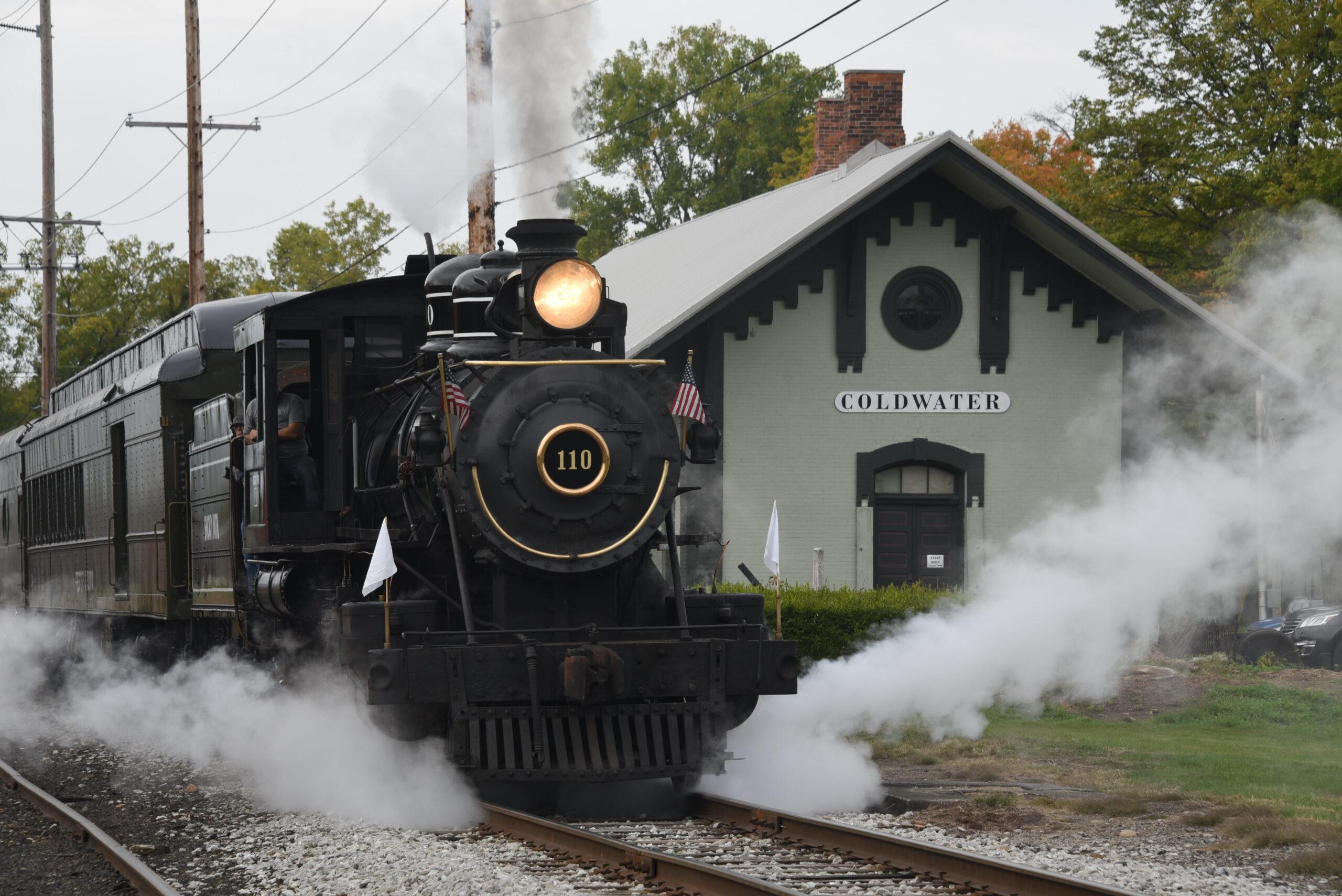 Small black steam locomotive departs train station.