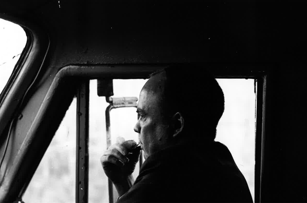 Black and white photo of man in locomotive cab