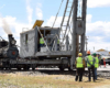 Operating railroad pile driver with crews looking on.