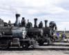 Four steam locomotives line for display in a rail yard.