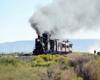 Double-headed steam passenger train high steps over the high plains.