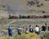 Steam hauled passenger train in open grassland.